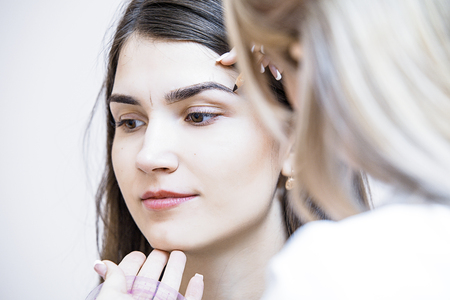 美容師の女性は、化粧品キャビネットの美しいモデル上の眉毛の補正を行います 写真素材