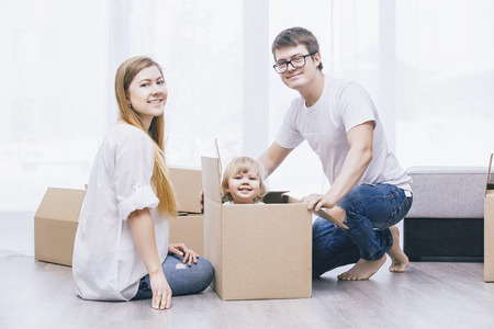 Family together happy young beautiful with a little baby moves with boxes to a new home 版權商用圖片