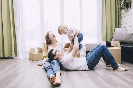 Glückliche junge schöne Familie zusammen mit einem kleinen Baby zieht mit Kästen in ein neues Haus um