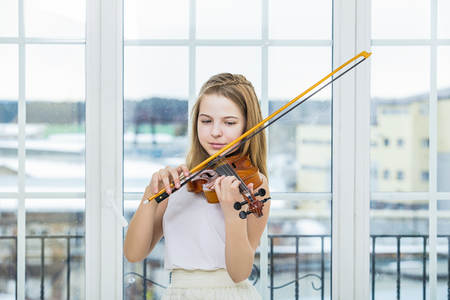 Child girl playing the violin to study beautiful and happy in a white room with a large window