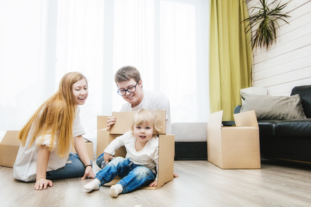 Family together happy young beautiful with a little baby moves with boxes to a new home Archivio Fotografico