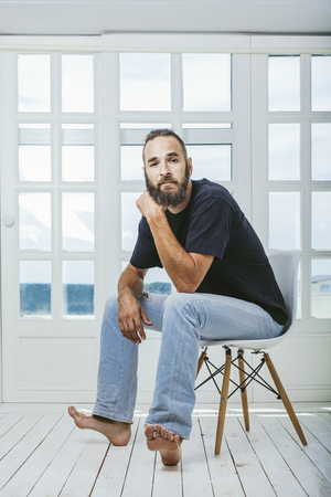 Young man in jeans with a beard a hipster sitting on a chair on the background of white window Stock Photo