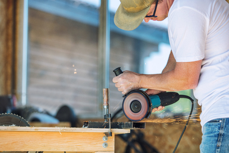 Adult young man working in a carpenters shop working with tools on the product