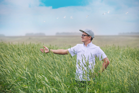 Man young farmer in the field of cereals admires the expanses and harvest 版權商用圖片