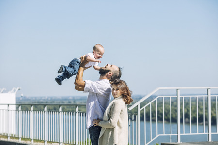 Family mom dad and baby happy with smiles together in the Park walking along the promenade in summer portrait
