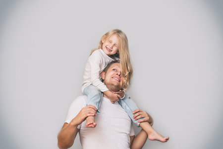 Father with a little daughter in his arms laughing happy and playing on a gray background in the Studio
