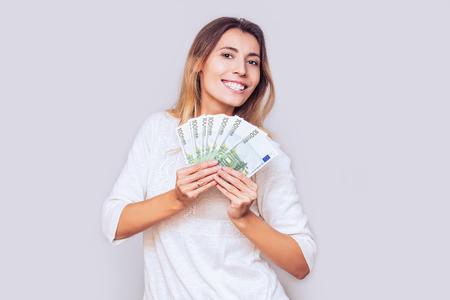 Femme jeune adulte heureux et émotionnel avec un fan d'argent euro européen dans le studio