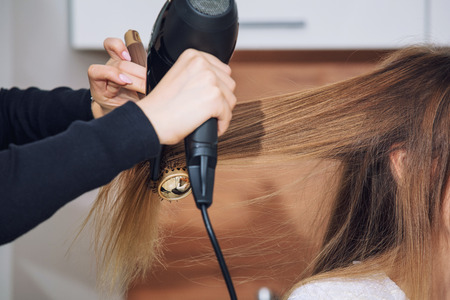 Young beautiful woman client doing styling at a professional hairdresser in a beauty salon close-up Imagens