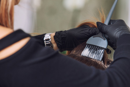 Young beautiful client hair coloring from a professional hairdresser in a beauty salon close-up