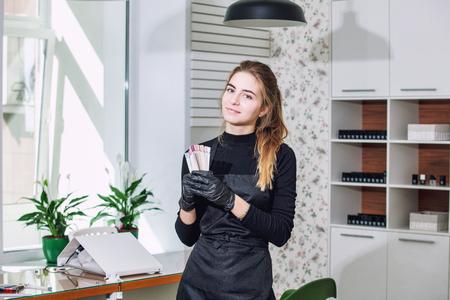 Manicure jonge mooie vrouw met een glimlach en professionele instrumenten in de handen van een schoonheidssalon Stockfoto