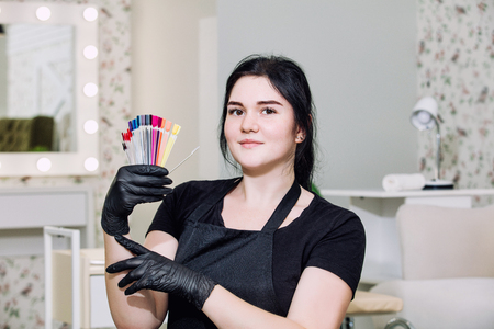 Manicurist young beautiful woman with a smile and professional tools in the hands of a beauty salon