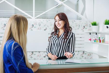 Bella ragazza giovane receptionist con un sorriso alla reception incontra i clienti nel salone