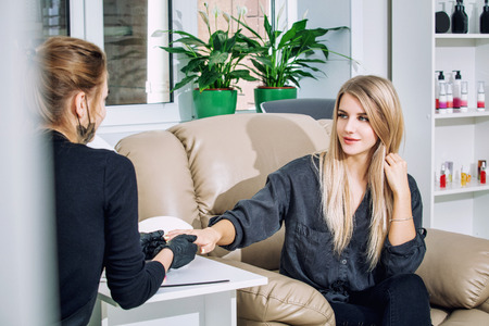 Young beautiful woman client makes a manicure with a professional manicure master in a beauty salon