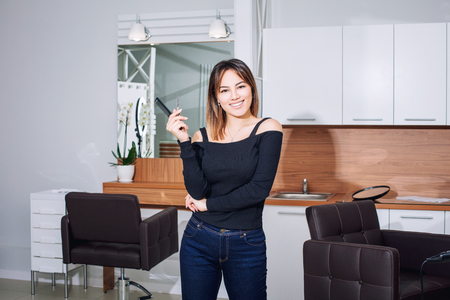 Master hairdresser young beautiful woman with smile and professional tools in hand in beauty salon Stock Photo