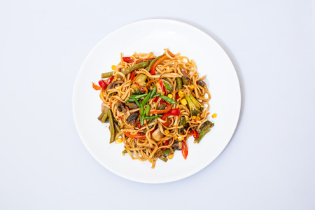 Wok food on a white ceramic plate is tasty and fresh with sauce on a light isolated background Stock fotó