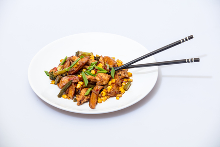 Wok food on a white ceramic plate is tasty and fresh with sauce on a light isolated background 스톡 콘텐츠