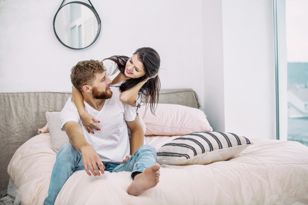 Young beautiful and happy couple man and woman at home in bedroom in bed romantic and in love
