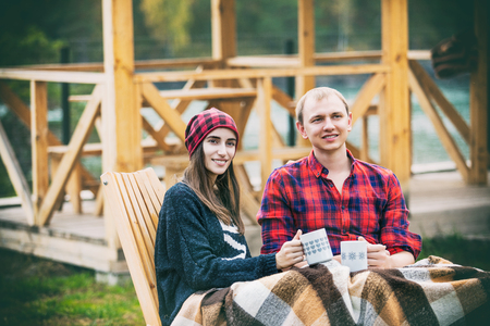 Couple man and woman young beautiful happy backyard outdoors with mugs with hot drinks Stock Photo