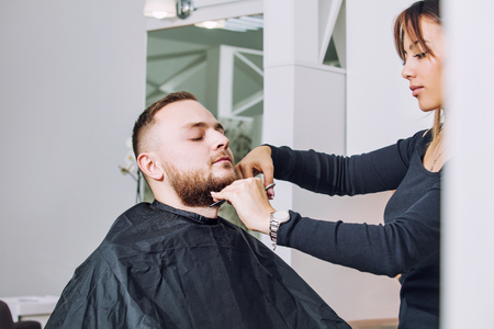 Young man with a beard on a haircut and beard design at the hairdresser in the beauty salon