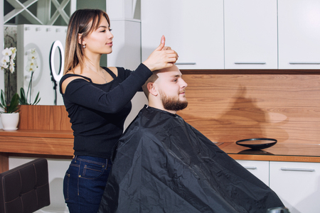 Young man with a beard on a haircut and beard design at the hairdresser in the beauty salon Stock Photo - 109321350