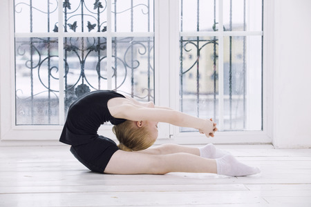 Little Child Girl gymnast doing stretching in a bright room on a happy and cute window background