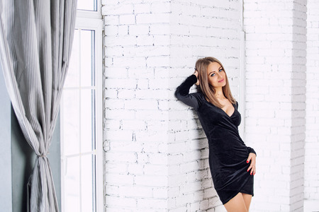 Young beautiful blonde girl and model in the interior in a fashionable dress on the background of Windows and white wall