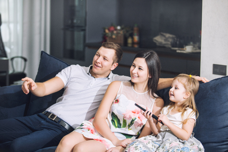 Family father, mother, daughter together beautiful and happy at home together on the couch watching telephoto