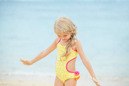 Little baby girl is beautiful and happy in a bright swimsuit in the afternoon on a Sunny beach