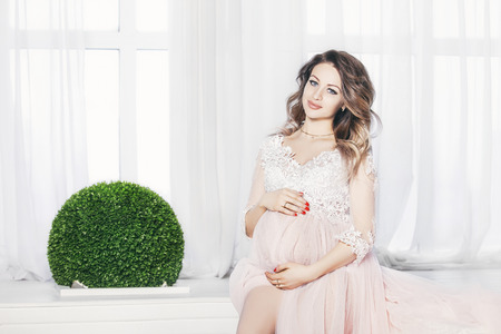 Beautiful young pregnant woman in Studio in light flying peignoir dress in white interior