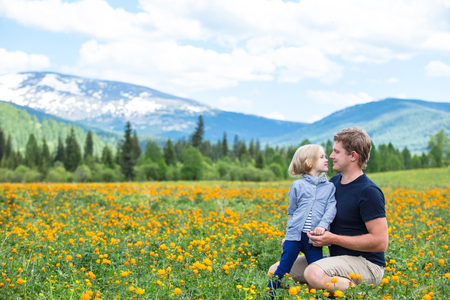 Dad and little daughter family beautiful and happy, smiling together in the summer in the meadow against the mountains with snow