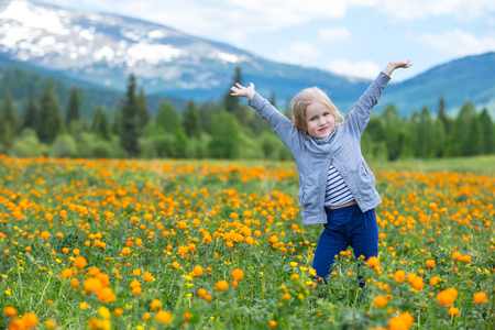 Little cute baby girl is beautiful and happy, smiling in summer in the meadow against the mountains with snow