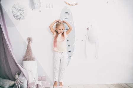 Little beautiful child girl in the childrens playroom measures her height