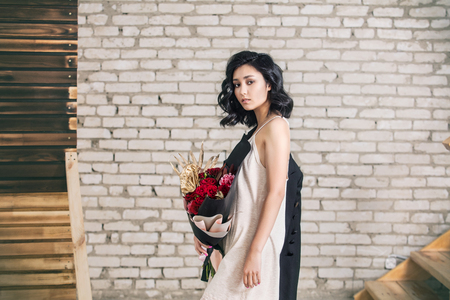 Young beautiful girl model with bouquet of flowers on brick wall background Stock Photo