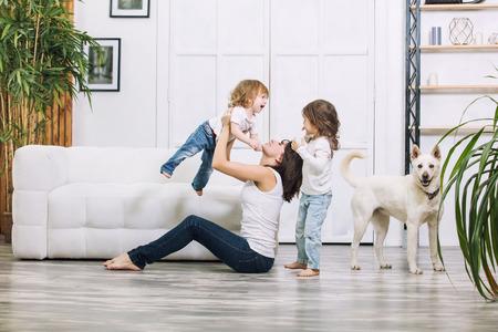 Kleine kindermeisjes zijn mooi en schattig met moeder en hond thuis samen gelukkig