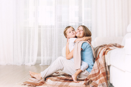 Happy and beautiful mother and child, family together at home in the living room