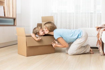 Happy and beautiful mother and child, family together in a new home with cardboard boxes