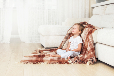 Happy and beautiful baby smiling at home in the living room sitting on the floor on a blanket Stock Photo