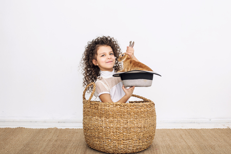 Child girl beautiful cute cheerful and happy in a wicker basket with small animals rabbit in a hat on a white wall background