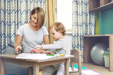 Happy and beautiful mother and child, family together draw on the table in the childrens colored markers