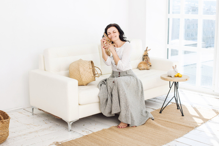 Young adult beautiful woman with fluffy rabbits and Easter eggs sitting on a white sofa in a stylish eco-friendly interior Stock Photo