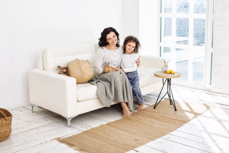 Mother and daughter cute beautiful and happy with rabbits and Easter eggs at home together Stock Photo