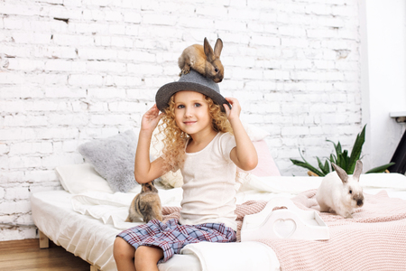 Beautiful child girl with curly hair and fluffy rabbits animals sitting on a hat