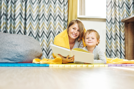 Happy and beautiful mother and child, family together reading a book lying in the nursery under the covers Imagens