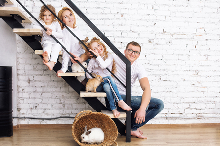 Happy family mother, father, two daughters and furry animal rabbits sitting at home on the stairs Imagens