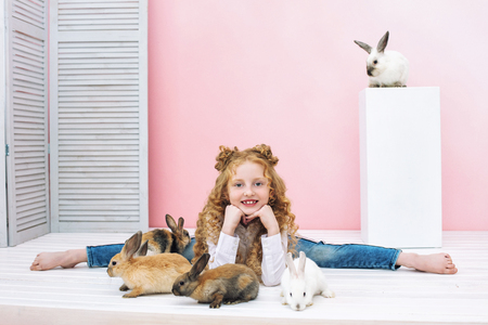Beautiful child girl with curly hair and with fluffy animals rabbits on pink background