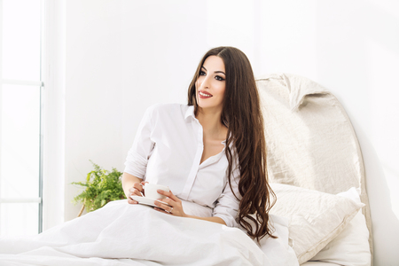 Young beautiful woman drinking from a mug of a hot drink at home in the bedroom in a white shirt in the morning