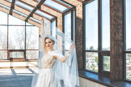 Junge schöne luxuriöse glückliche Braut in einem modischen Hochzeitskleid in der Halle mit großen Fenstern
