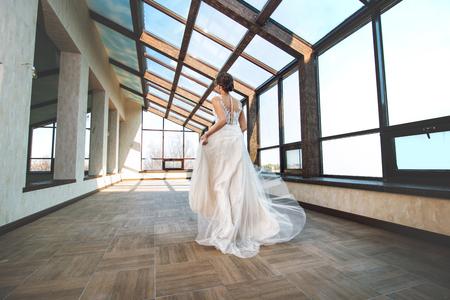 Junge schöne luxuriöse glückliche Braut in einem modischen Hochzeitskleid in der Halle mit großen Fenstern Standard-Bild