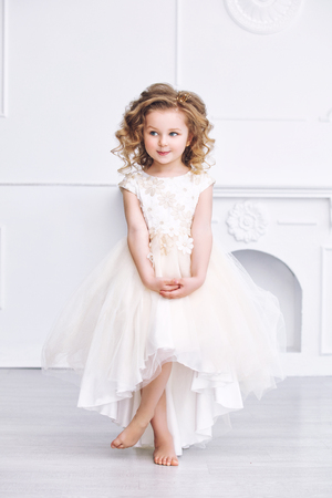 Little beautiful and cute girl child in a fashionable festive dress in a white interior