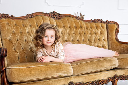Little beautiful and cute girl in a fashionable festive dress on a luxurious vintage sofa Stockfoto
